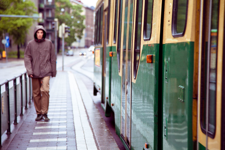 Summer Day in Helsinki - man walks beside a tram the streets glisten with rain