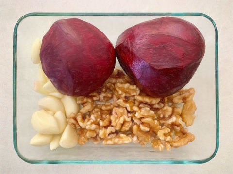 Peeled beetroot and garlic cloves with walnuts ready to roast